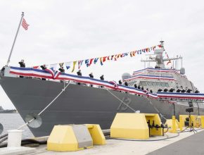 A decorated Navy ship alongside a pier