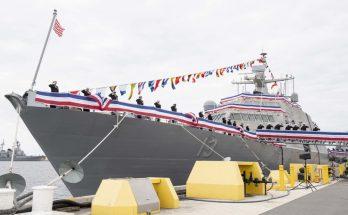 A decorated Navy ship alongside a pier