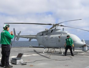 Unmanned Navy helicopter on a flight deck with two crew members