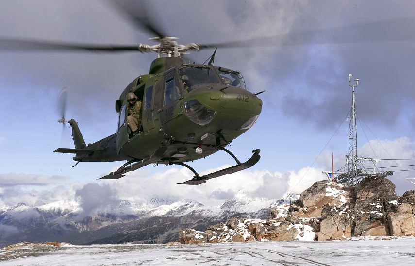 A Canadian helicopter flying in the snowy mountains