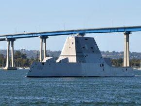 A Navy ship sails under a bridge